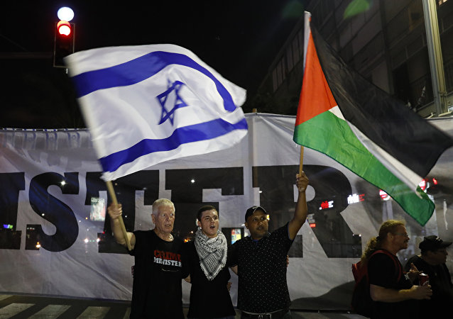 Arab Israelis and their supporters carry a Palestinian (R) and an Israeli flag during a demonstration to protest against the 'Jewish Nation-State Law' in the Israeli coastal city of Tel Aviv on August 11, 2018.
