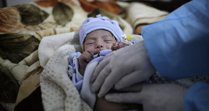 a doctor checks a two-month-old infant suffering from a cholera infection, at Al-Sabeen hospital, in Sanaa, Yemen, on March 30, 2019