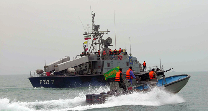A picture released by the official Iranian News Agency shows members of Iran's elite Revolutionary Guard riding their boat along with an Iranian naval vessel during manoeuvers along the Gulf Sea and Sea of Oman, 03 April 2006