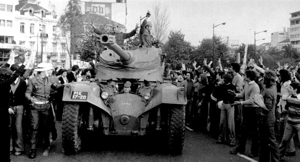 People cheer Portuguese soldiers in a tank driving in Lisbon during the Carnation Revolution in 1974