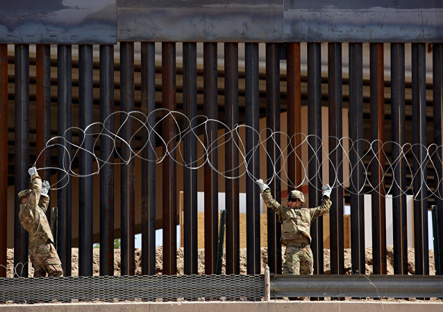U.S. soldiers install concertina wire next to the border fence between Mexico and the United States, in El Paso, Texas, U.S., in this picture taken from Ciudad Juarez, Mexico, April 4, 2019