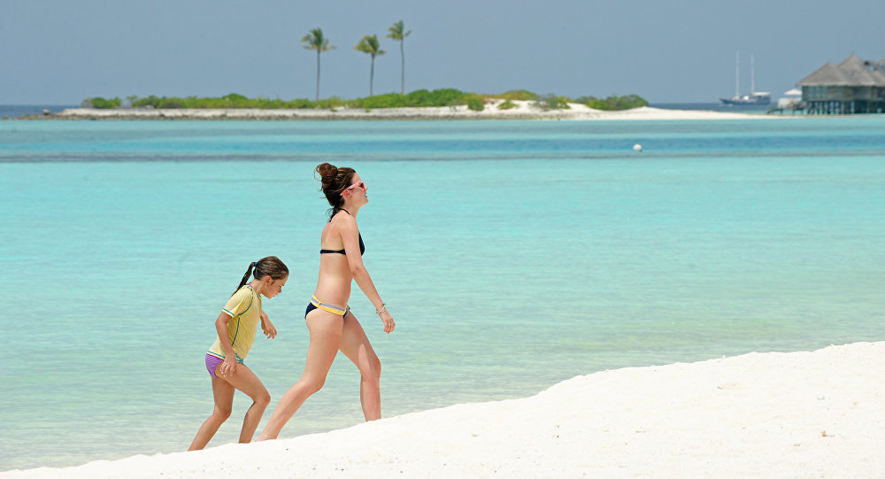 Unidentified foreign tourists walk along a beach of the Paradise Island Resort and Spa in the North Male' Atoll on February 14, 2012