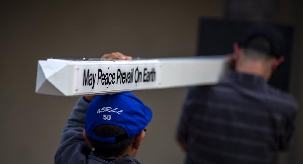 Boys carry a peace pole to an interfaith prayer and candlelight vigil at Rancho Bernardo Community Presbyterian Church on April 27, 2019 in Poway, California.