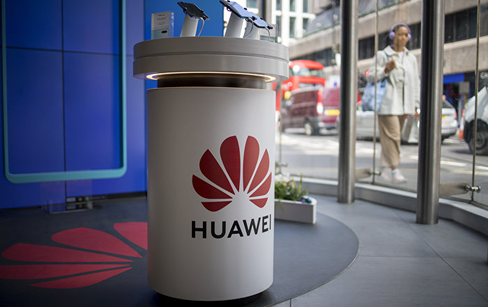 A pedestrian walks past a Huawei product stand at an EE telecommunications shop in central London on April 29, 2019