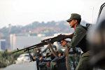 A military member aims a weapon near the Generalisimo Francisco de Miranda Airbase La Carlota, in Caracas, Venezuela April 30, 2019