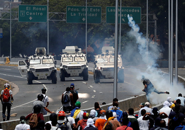 Opposition demonstrators face military vehicles near the Generalisimo Francisco de Miranda Airbase La Carlota in Caracas
