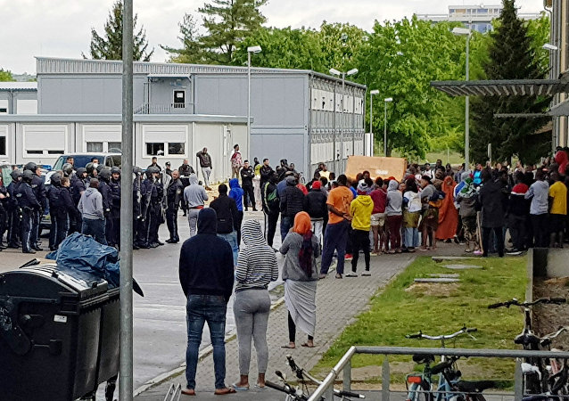 German police officers and migrants stand in front of an asylum center after a woman was found dead in the center in Regensburg, Germany, Saturday, May 11, 2019