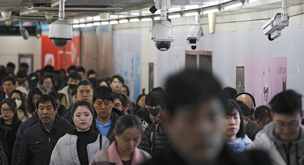 Commuters walk by surveillance cameras installed at a walkway in between two subway stations in Beijing, Tuesday, Feb. 26, 2019