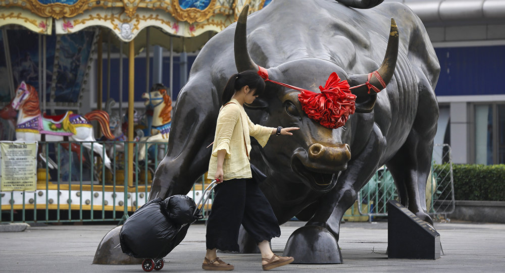 A woman pulls a 2 wheel trolley loaded with goods touches a bull statue on display outside a retail and wholesale clothing mall in Beijing, Monday, July 9, 2018