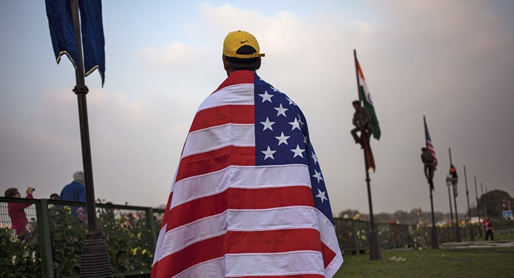 An Indian worker wears an American flag before it is hoisted up a flag pole in New Delhi, India, Friday, Jan. 23, 2015