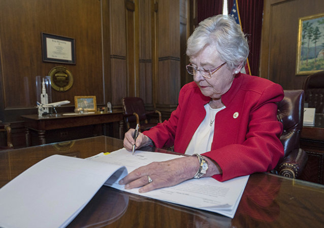 This photograph released by the state shows Alabama Gov. Kay Ivey signing a bill that virtually outlaws abortion in the state on Wednesday, May 15, 2019, in Montgomery, Ala.