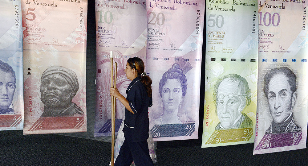 A woman walks past banners portraying the Venezuelan currency, the Bolivar, at the Venezuelan Central Bank in Caracas
