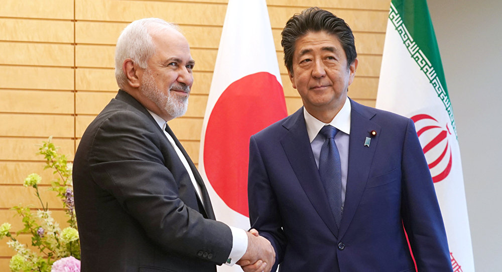 Iranian Foreign Minister Mohammad Javad Zarif, left, and Japanese Prime Minister Shinzo Abe, right, shake hands at Abe's official residence in Tokyo Thursday, May 16, 2019