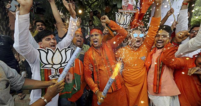 Bharatiya Janata Party (BJP) workers celebrate outside BJP headquarters in New Delhi India, Thursday, May 23, 2019.