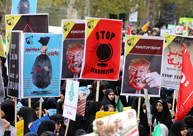 Iranian women carrying placards, some bearing the portrait of US President Donald Trump, during a demonstration outside the former US embassy in the Iranian capital Tehran on November 4, 2017, marking the anniversary of its storming by student protesters that triggered a hostage crisis in 1979