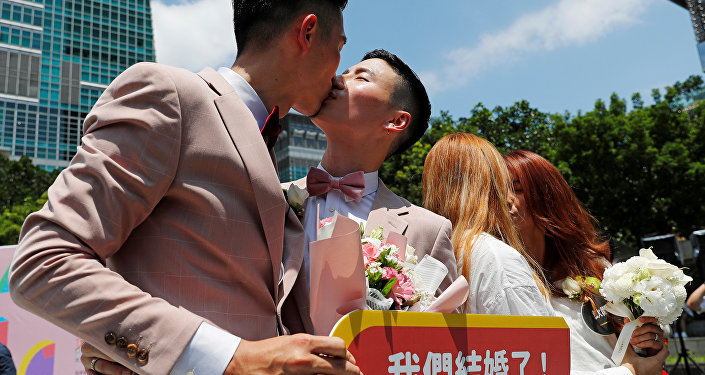 Gay and lesbian newlyweds kiss at a pro same-sex marriage party after registering their marriages in Taipei