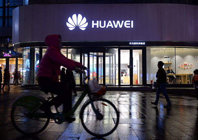 A woman cycles past a Huawei store in Shenyang, Liaoning province, China on 20 March 2019