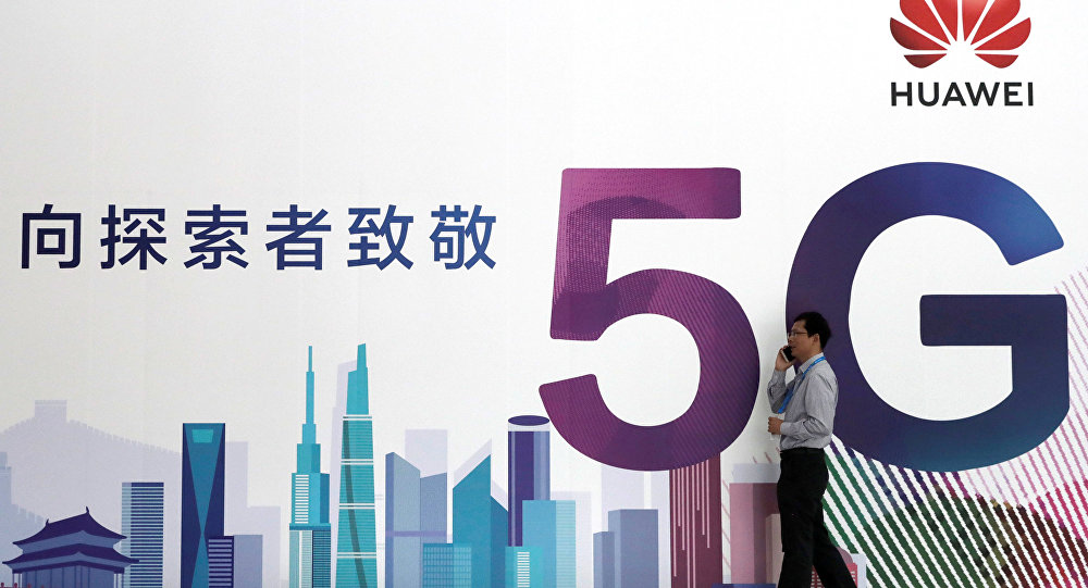 A man talks on his mobile phone beside Huawei's billboard featuring 5G technology at the PT Expo in Beijing, China, September 26, 2018