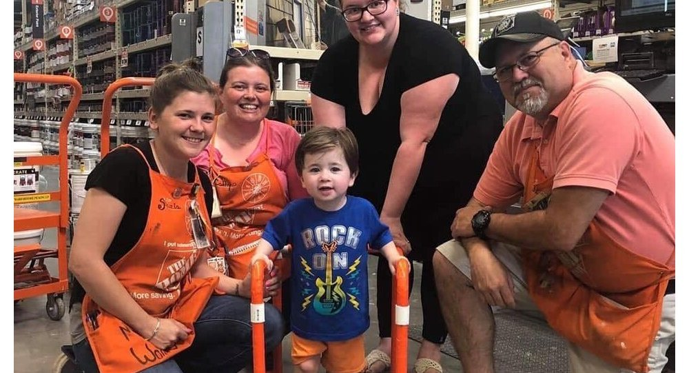 Toddler and his family pose with Home Depot workers who donated and assembled the two-year-old's PVC walker