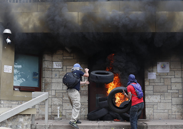 Protesters add tires to a fire outside the main entrance into the U.S. Embassy during a protest against the government of President Juan Orlando Hernandez, in Tegucigalpa, Honduras, Friday, May 31, 2019.