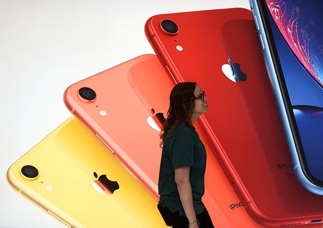 An Apple Store employee walks past an illustration of iPhones at the new Apple Carnegie Library during the grand opening and media preview in Washington, U.S., May 9, 2019