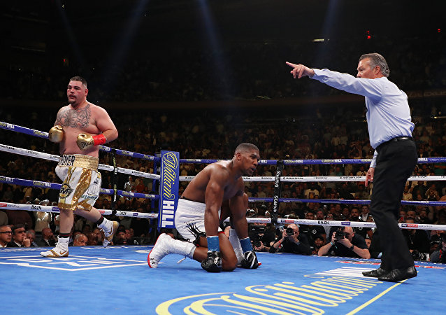 Anthony Joshua touches down on the canvas as the ref orders Andy Ruiz to a neutral corner during their 1 June 2019 clash