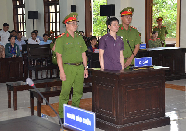 Vietnamese Facebook user Nguyen Ngoc Anh stands between policemen during his trial at a court in Ben Tre province