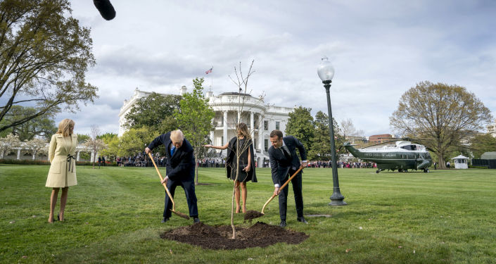 FILE - In this April 23, 2018, file photo, first lady Melania Trump, second from right, and Brigitte Macron, left, watch as President Donald Trump and French President Emmanuel Macron participate in a tree planting ceremony on the South Lawn of the White House in Washington. The oak sapling that was a gift to Trump from Macron is facing at least two years in quarantine. (AP Photo/Andrew Harnik, File)