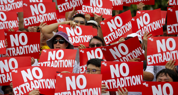 Protesters hold placards as they stage protest against the extradition law in Hong Kong, Sunday, June 9, 2019