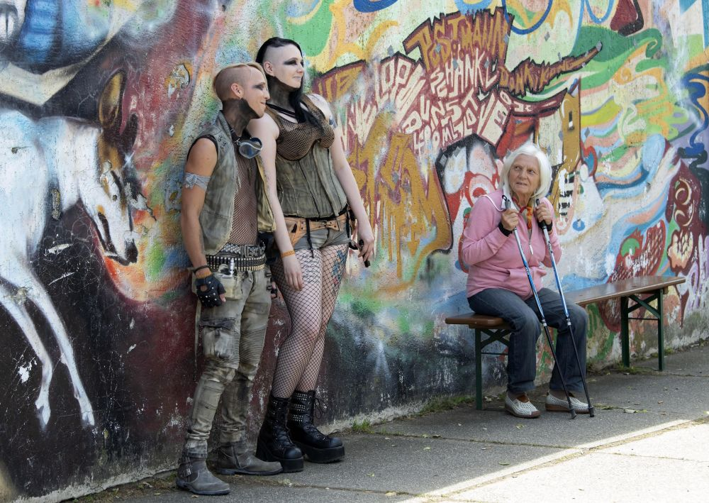 Participants in fancy costumes pose for photographers besides a woman during the Wave Gothic Festival (WGT) in Leipzig, Germany, Saturday, June 8, 2019. Approximately 20,000 goths and other dark subculture fans such as cybergoths, metalheads, steampunks, neo-Victorians, dark romantics, dark electro, industrial, medieval and fetish fans are expected to attend the world's largest gothic and 'dark' culture festival until June 10, 2019.
