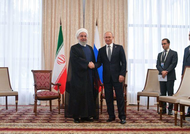 Russian President Vladimir Putin shakes hands with Iranian President Hassan Rouhani, left, during their meeting at the Shanghai Cooperation Organization (SCO) summit, in Bishkek, Kyrgyzstan