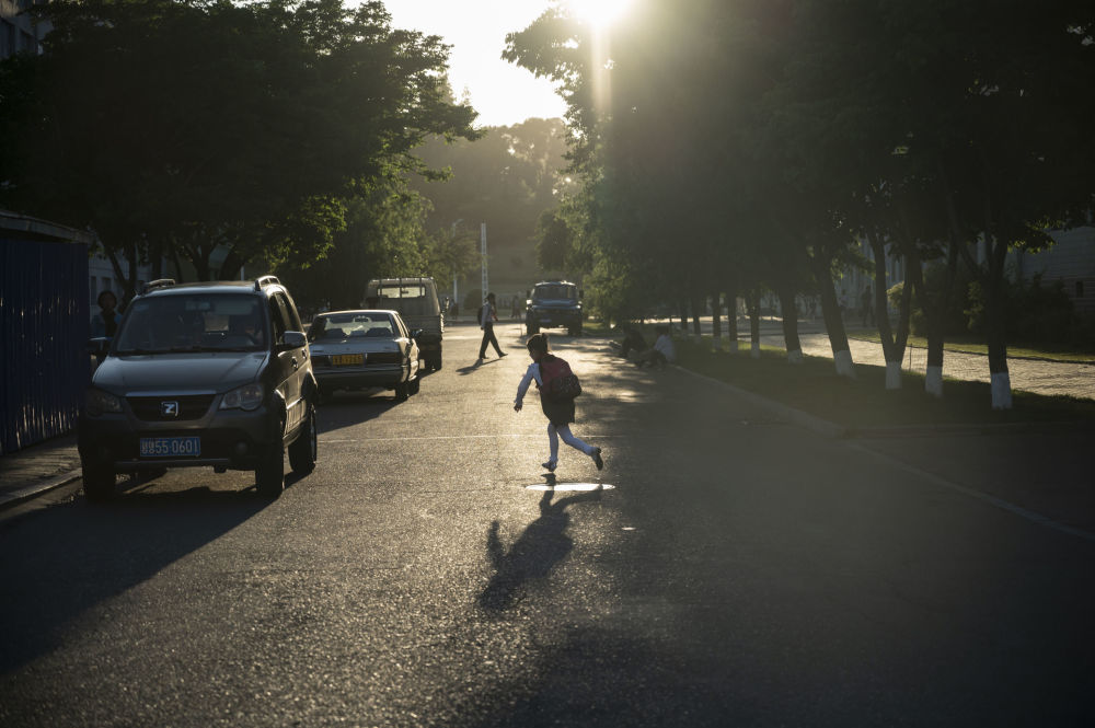 A child runs at a sun-drenched street in the North Korean capital.