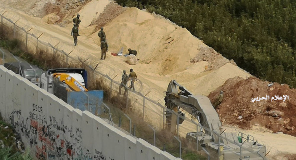 In this photo released by Hezbollah Central Military Media, Israeli military digger work on the Lebanese-Israeli border next to a wall that was built by Israel in the southern village of Kafr Kila, Lebanon on Tuesday, Dec. 4, 2018.