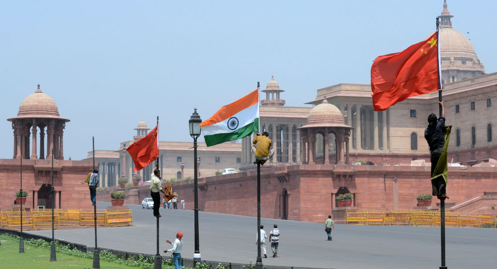 Indian workers tie Indian and Chinese national flags onto poles in front of The Indian Secretariat in New Delhi on May 18, 2013