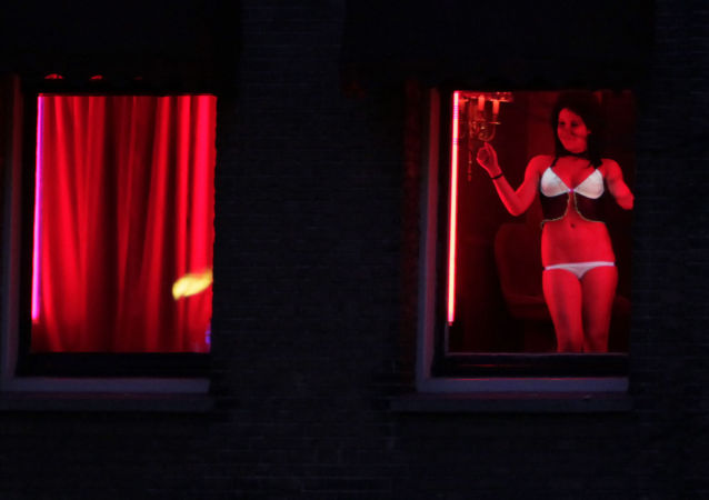 In this photo, taken on 10 January 2011, a prostitute plies her trade behind red-lit windows in Amsterdam, Netherlands