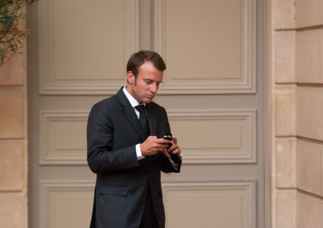 Emmanuel Macron, looks at his phone