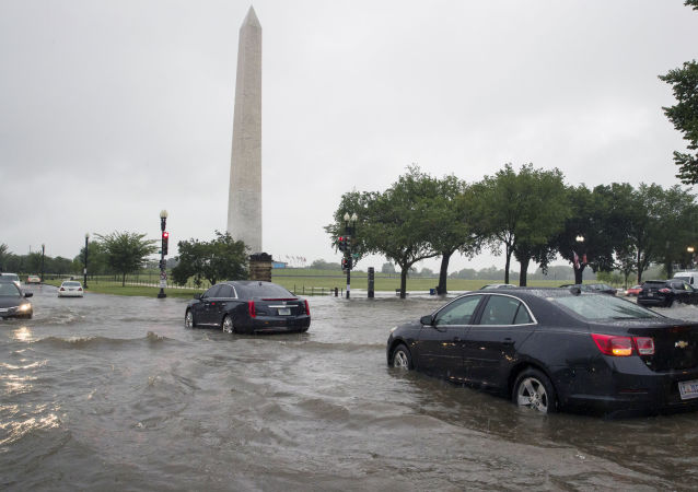 Heavy rainfall flooded the intersection of 15th Street and Constitution Ave., NW stalling cars in the street, Monday, July 8, 2019, in Washington near the Washington Monument.