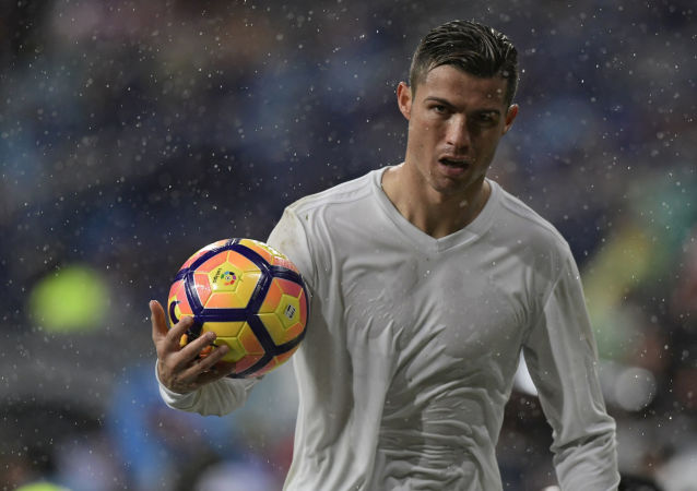 Real Madrid's Portuguese forward Cristiano Ronaldo holds a ball during the Spanish league football match Real Madrid CF vs Sporting de Gijon SAD at the Santiago Bernabeu stadium in Madrid on November 26, 2016