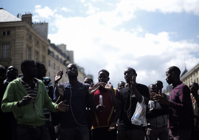 Migrants shout outside the Pantheon monument, where illustrious French figures are buried, in the Latin quarter of Paris, Friday, July 12, 2019. Dozens of migrants invaded the Pantheon. (AP Photo/Kamil Zihnioglu)