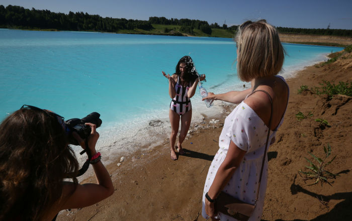 A young woman poses for pictures by a Novosibirsk energy plant's ash dump site - nicknamed the local Maldives - on 11 July 2019.