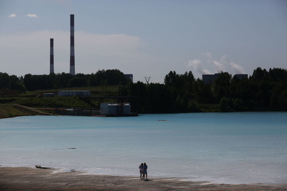 A couple walks by a Novosibirsk energy plant's ash dump site.