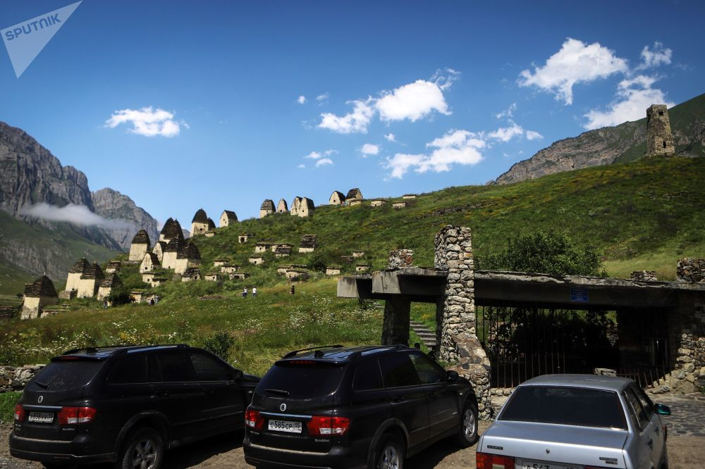 Cars parked near necropolis on the territory of the 'City of the Dead' in Russia's republic of North Ossetia