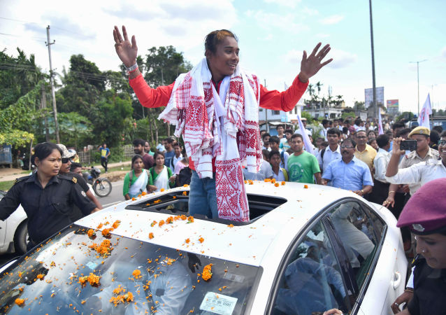 Indian sprinter Hima Das (C) waves as she arrives in Guwahati on September 7, 2018