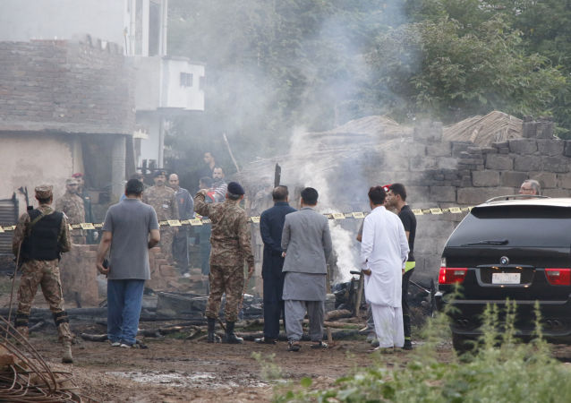 Pakistani soldiers and officers survey the site after a military aircraft on a training flight crashed in the garrison city of Rawalpindi, Pakistan, 30 July 2019