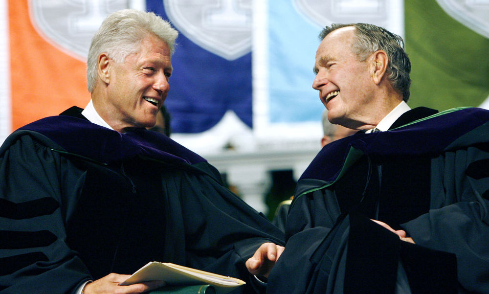 Former Presidents Bill Clinton, left, and George H. W. Bush smile at each other on the podium at the Tulane University Commencement in New Orleans on 13 May, 2006.