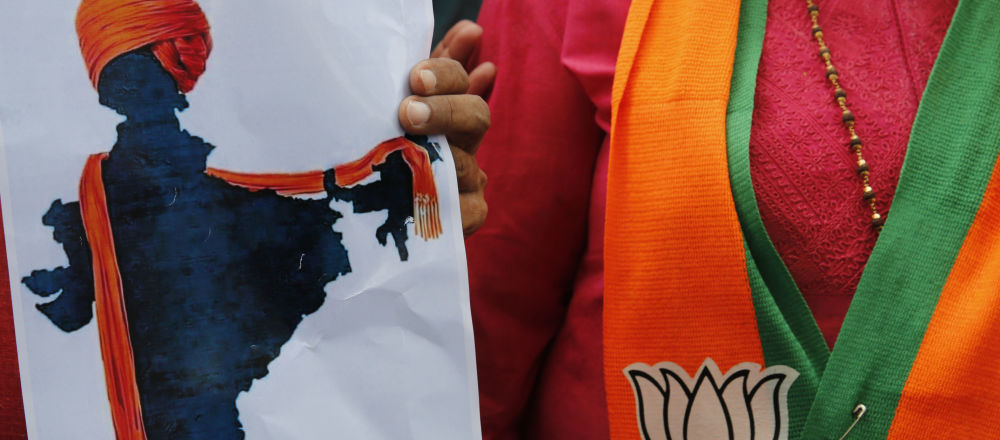 A participant displays an artist's impression of the India map decorated with a saffron shawl as ruling Bharatiya Janata Party (BJP) supporters celebrate government revoking disputed Kashmir's special status in Prayagraj, India, Monday, Aug. 5, 2019.