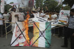 Pakistanis burn a poster of Indian Prime Minster Narendra Modi during a protest to express support and solidarity with Indian Kashmiri people in their peaceful struggle for their right to self-determination, in Lahore, Pakistan, Monday, Aug. 5, 2019. India's government has revoked disputed Kashmir's special status by a presidential order as thousands of troops patrolled and internet and phone services were suspended in the region where most people oppose Indian rule. (AP Photo/K.M. Chaudary)