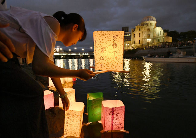 Girl releases paper lanterns on the Motoyasu River facing the gutted Atomic Bomb Dome in Hiroshima