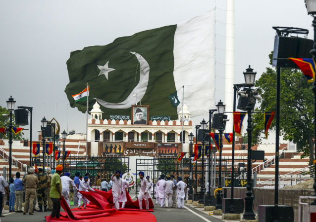 Sikh devotees fold a red carpet as the Pakistani flag is being taken off due to dark clouds looming over at the India-Pakistan Wagah Border, near in Amritsar on August 1, 2019