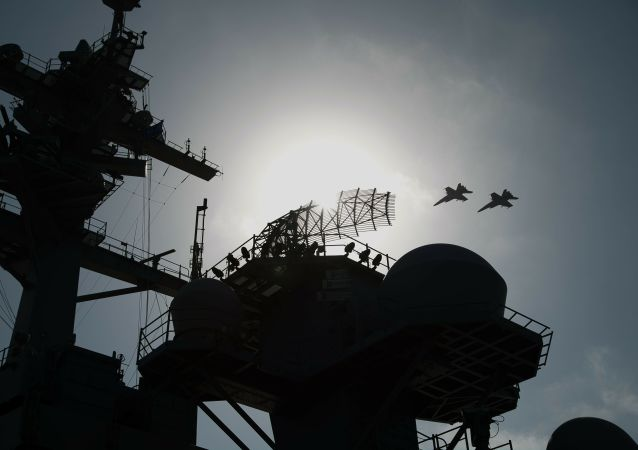 F/A-18 fighter jets fly over the deck of the USS Abraham Lincoln aircraft carrier in the Arabian Sea, Monday, June 3, 2019